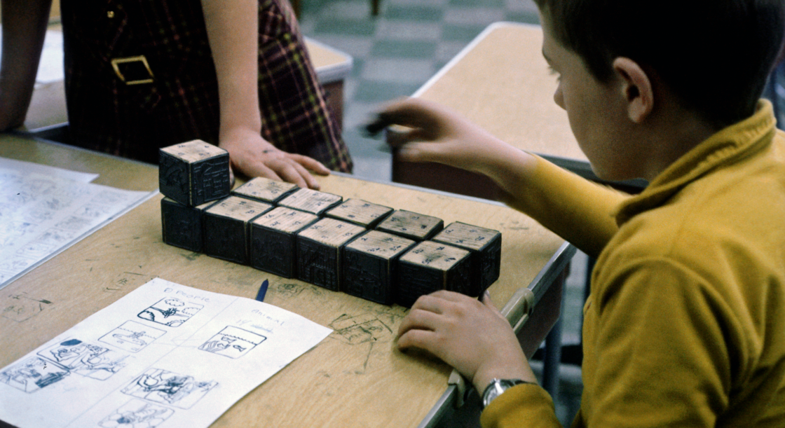 A child with ink on his hands sits at a school, playing with a matching game from the EDC.